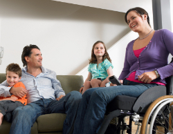 A woman smiling and surrounded by a man and two young children; the woman is in a wheelchair