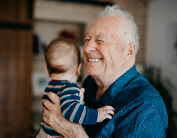 An older man with a large, happy smile, hugging a toddler